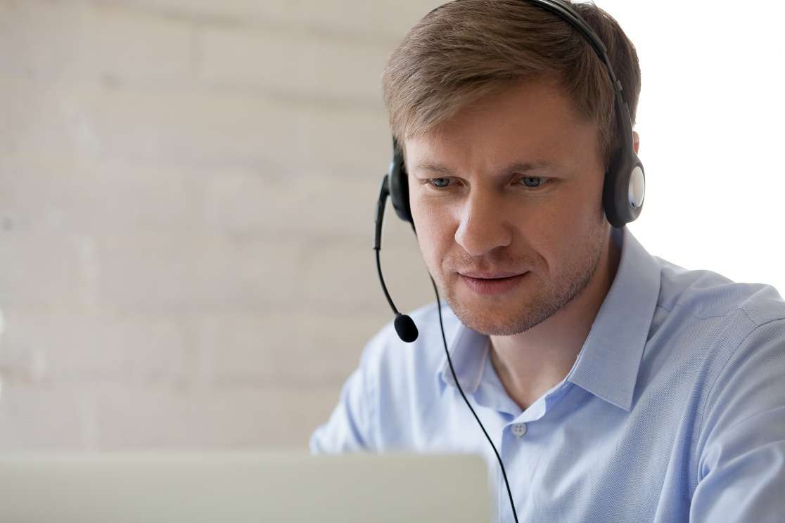 Millennial support hotline worker with laptop and headphones at workplace
